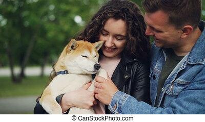 Slow motion of happy couple holding beautiful pedigree dog,...
