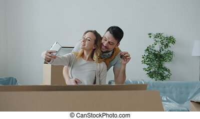Slow motion of happy young couple taking selfie in new apartment holding key kissing posing for smartphone camera in room full of cardboard boxes