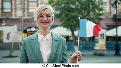 Slow motion of happy French girl holding national flag...