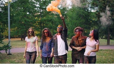 Slow motion of happy friends with painted faces walking in park holding smoke pellet and smiling, bright orange smoke is rising up. Fun and people concept.