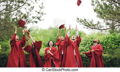 Slow motion of happy graduates throwing mortarboards in air, laughing and celebrating graduation on college campus. Education, success and modern youth concept.