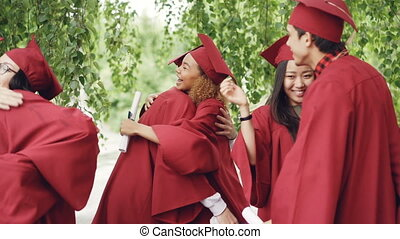 Slow motion of happy graduates wearing gowns and mortar-boards hugging, laughing and congratulating each other on graduation day. Happiness and youth concept.