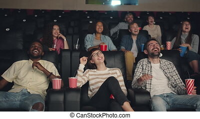 Slow motion of happy millennials laughing in cinema watching...
