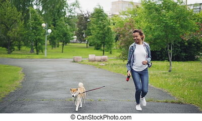 Slow motion of happy mixed race girl running in city park with beautiful small dog enjoying nature, freedom and outdoor activity. Healthy lifestyle concept.