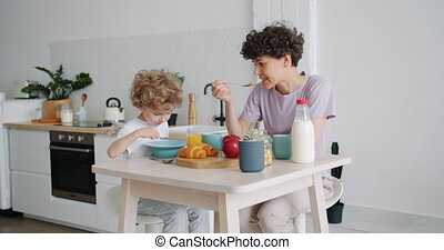 Slow motion of happy mother and son eating cereal with milk...