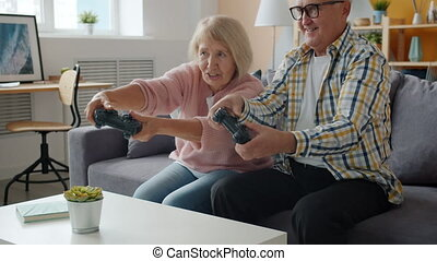 Slow motion of happy old people playing video game at home enjoying leisure fun
