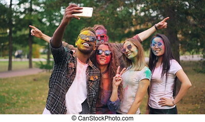 Slow motion of happy students multiethnic group with coloured faces and hair taking selfie in park using smartphone camera and having fun at Holi festival.