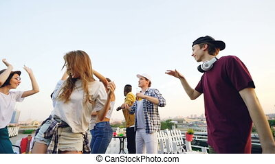 Slow motion of happy students partying on rooftop dancing and laughing holding drinks while DJ is working with music mixer. Youth, fun and leisure concept.