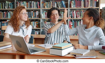 Slow motion of happy students studying in library doing high-five laughing