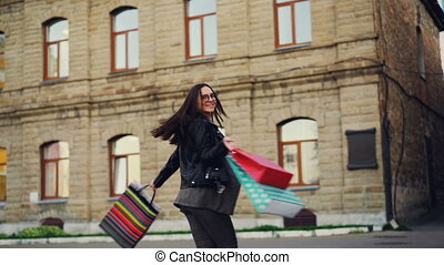 Slow motion of happy young lady shopaholic dancing in the street with shopping bags turning spinning looking at camera. Urban lifestyle and consumerism concept.