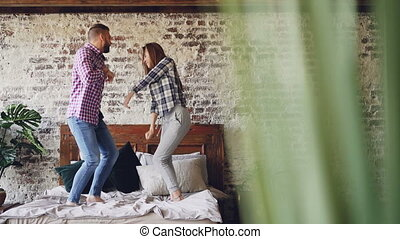 Slow motion of happy young lovers dancing on double bed...