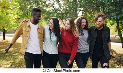 Slow motion of happy young people friends walking together...