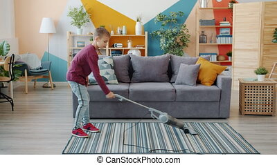 Slow motion of helpful little boy vacuuming floor at home using vacuum cleaner doing housework alone. Childhood, lifestyle and housekeeping concept.