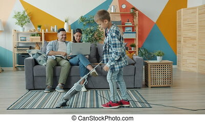 Slow motion of helpful son vacuuming carpet on floor while parents mother and father are using laptop sitting on sofa at home. Family and housekeeping concept.