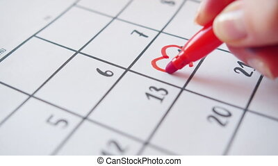 Slow motion of human hand drawing heart shape around 14 February in calendar using bright red marker waiting for joyful celebration. People and romance concept.