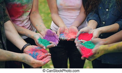 Slow motion of human hands holding multicolor powder paint...