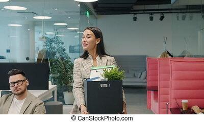 Slow motion of joyful businesswoman leaving work with box of belongings smiling quitting saying good-bye to former coworkers. People and job concept.