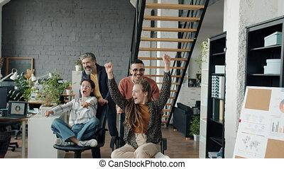 Slow motion of joyful employees men and women having fun in office riding chairs enjoying work break together. Happy people and workplace concept.