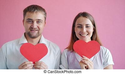 Slow motion of joyful loving couple hiding faces behind ...