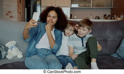 Slow motion of joyful people babysitter and children taking selfie with smartphone camera having fun