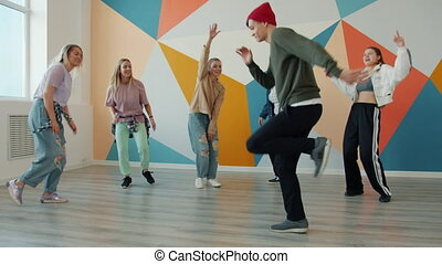 Slow motion of joyful youth dancing in dance hip-hop studio wearing trendy clothing, modern colorful interior is visible. People and occupation concept.