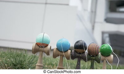Slow motion of kendama toys being blown away by the wind