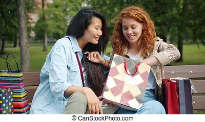 Slow motion of ladies looking at purchases in shopping bags ...