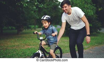 Slow motion of cute laughing child cycling in park with careful father who is teaching him to ride bicycle. Happy young family, fatherhood and childhood, active lifestyle concept.