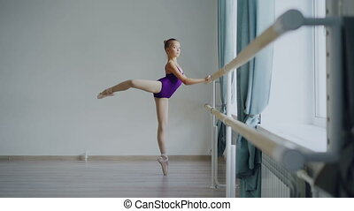 Slow motion of little ballet-dancer standing on tiptoes and...
