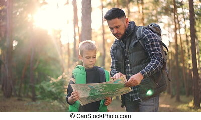 Slow motion of little boy holding map standing in forest...