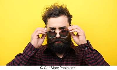 bearded hipster lowers his sunglasses on yellow background -...