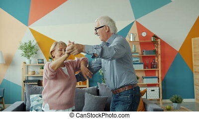 Slow motion of loving couple retired woman and man dancing at home together