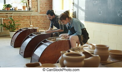 Slow motion of male and female ceramists working with ...