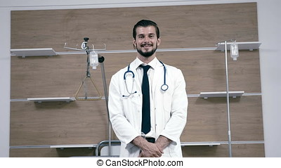 Slow motion of male doctor smiling at camera in hospital room
