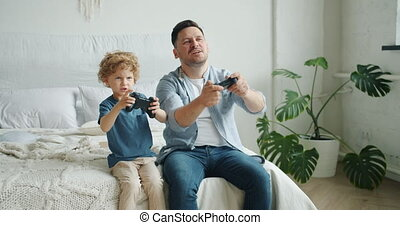 Slow motion of man and boy playing video game having fun sitting in bed at home