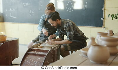 Slow motion of man and woman making pot of spinning wheel in...