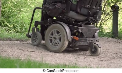 Slow motion of man in a wheelchair driving off road with obstacle on the road. disabled people problem concept