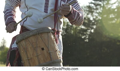 Slow motion of man in traditional russian clothes dancing and playing on folklore drum outdoor on traditional antique wooden windmill background. Man wearing national Finno-Ugric clothes.