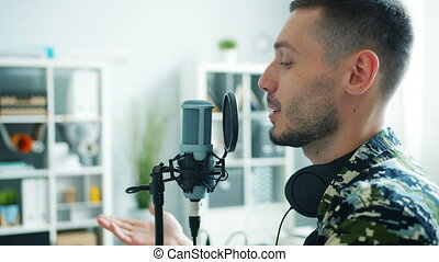 Slow motion of man talking in microphone recording audio in...