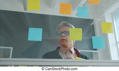 Slow motion of mature adult man sticking bright sticky notes on office glass wall working alone focused on creative activity. Businesspeople and work concept.