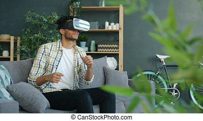 Slow motion of mixed race man enjoying game in augmented reality glasses moving hands and body sitting on couch at home. People and devices concept.