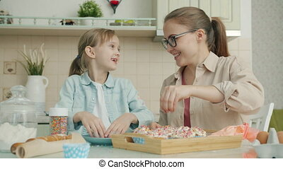 Slow motion of mother and daughter cooking together decorating pastry and talking in apartment
