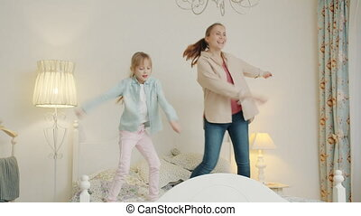 Slow motion of mother and daughter dancing in bed having fun together at home