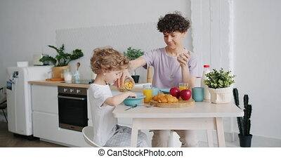 Slow motion of mother putting cereal on plate for small son...