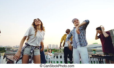 Slow motion of multi-ethnic group of friends dancing and relaxing at open-air party with DJ using professional equipment. Beautiful big city is visible in background.