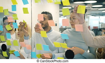 Slow motion of multi-ethnic team sticking colorful notes on ...