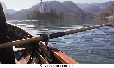 Slow motion of paddle rowing in a boat on lake Bled with...