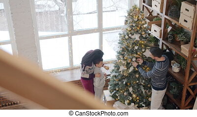 Slow motion of parents and child decorating New Year tree getting ready for winter holidays