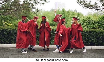 Slow motion of playful girls and guys graduating students...