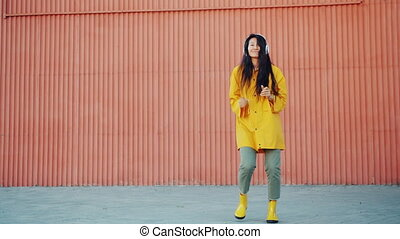 Slow motion of pretty young Asian girl dancing outdoors wearing raincoat and gumboots enjoying song in headphones. People, autumn and happiness concept.